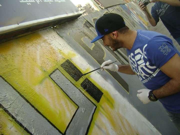 صور تامر حسني يكتب اسم شهداء التحرير على الجدار iqpiccb420543af.jpg